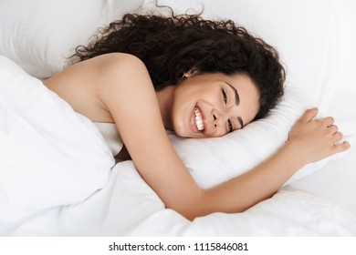 Image of beautiful woman 20s with dark curly hair smiling while lying in bed on white pillow after sleep or nap