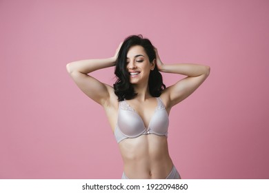 Image of a beautiful woman posing in lingerie on a pink colored background