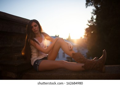 Image of a beautiful woman sitting on the railing.