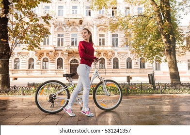 55d4595cc8 Image of beautiful woman walking with her bicycle in the city. Looking back.