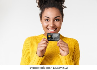 Image of a beautiful young african excited emotional happy woman posing isolated over white wall background holding credit card.