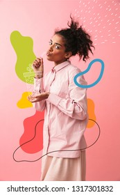 Image of a beautiful young african woman posing isolated over pink wall background imagine that she drinking tea.