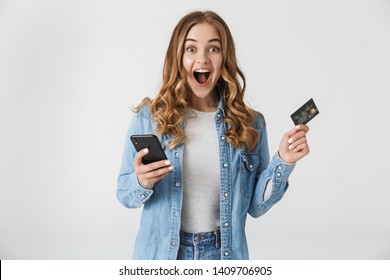 Image of a beautiful young excited pretty woman posing isolated over white wall background using mobile phone holding credit card.