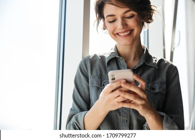 Image of beautiful young joyful woman using mobile phone and smiling while standing near window