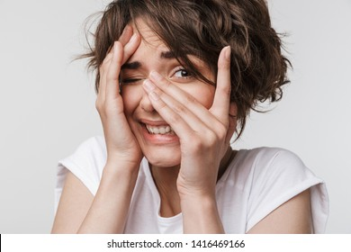 Image of a beautiful young pretty scared woman posing isolated over white wall background covering face.