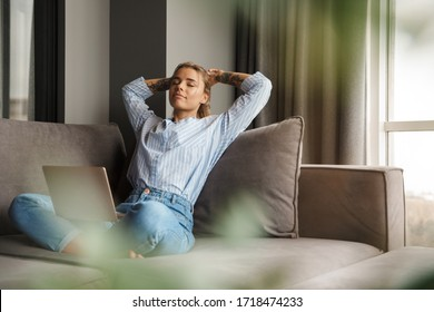 Image of beautiful young relaxed woman resting while sitting with laptop on sofa at living room