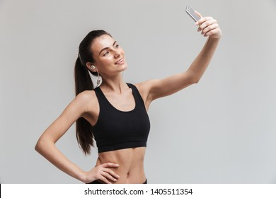 Image of a beautiful young sport fitness woman using mobile phone listening music isolated over grey wall background take a selfie.