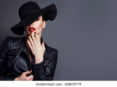 Image of a beautiful young woman with bright makeup, red lips and a black wide-brimmed hat. Vamp woman, glamor.
