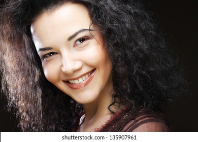 Image of beautiful young woman with curly hair over black background