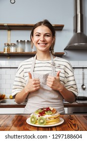 Image of a beautiful young woman in kitchen cooking and eat cake showing thumbs up.