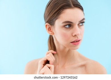 Image of beautiful young woman posing isolated over blue background.