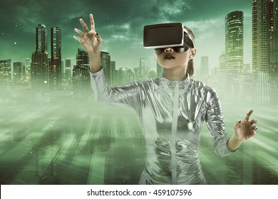 Image of beautiful young woman in silver latex costume and VR headset