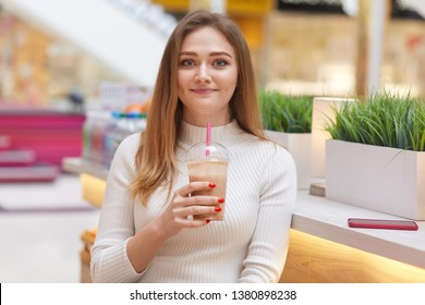 Image of beautiful young woman sits in cafe with cocktail, looks smiling at camere, has long bonde hair, dressed white casual sweater, being glad to have free time, attractive female. People concept.