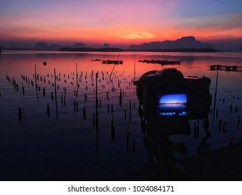 The image of beauty light of sunrise in the morning with dslr camera and tripod for traveler and photography lanscape anger at the sea and clear red sky.