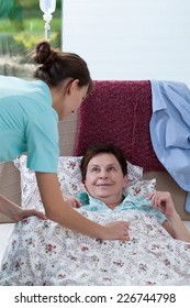 Image of bedridden woman and helpful nurse