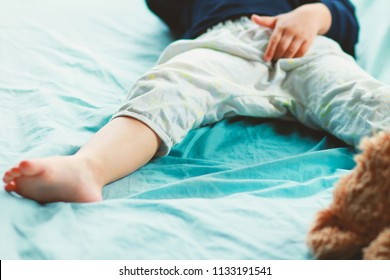 Image of Bed-wetting situation in  toddler baby boy.Boy wet the bed and touch his penis while he was sleeping.Selective focus.Stop using diaper or Potty training concept.
