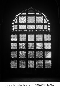 The image belongs to The Tomb of Muhammad Ghaus in Gwalior, Madhya Pradesh, India. It depicts a window inside the tomb with ornamental motif work.