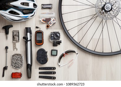 Image of bicycle objects on wooden background. Wheel, helm, seat, helmet, tire.
