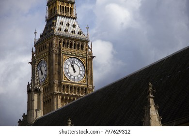 An image of the big ben tower, partly hidden by the building. Dark clouds in the background.