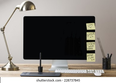 Image of a big computer screen with a lamp and stationary items