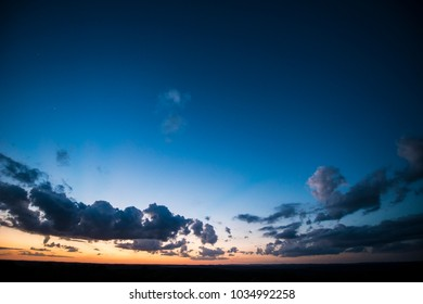 Image of a big Texas sky at dusk with a few clouds