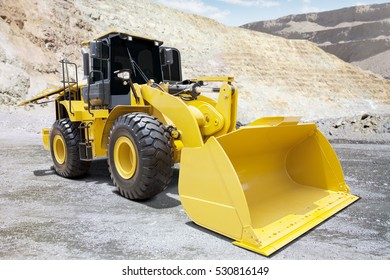 Image of a big wheel loader with yellow color and a big scoop on the mining site