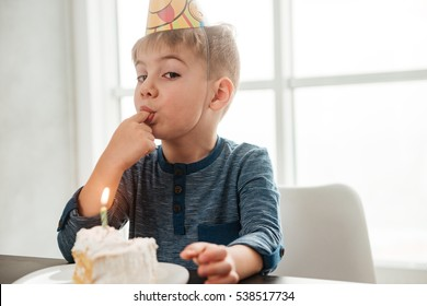 Image of birthday boy sitting in kitchen near cake and eating. Look at camera.
