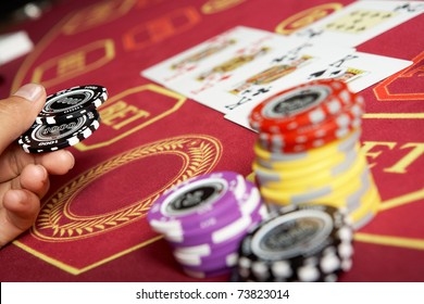 Image of black chips in hand over casino table