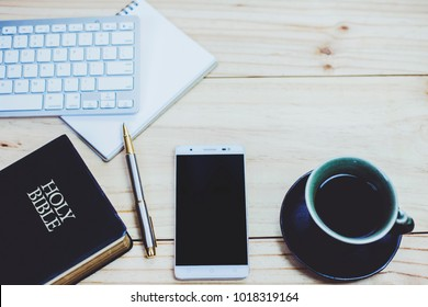 image of a black coffee cup on wooden background with smartphone over the small note book and burred of holy bible in background, vintage color, copy space