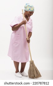 Image of a black domestic worker sweeping with a broom