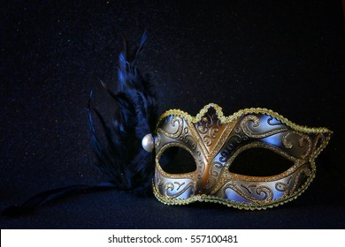 Image of black elegant venetian mask on glitter background