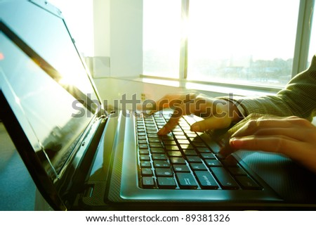 Image of black laptop keyboard with female hands touching it