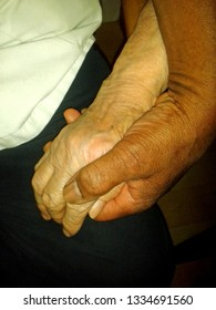Image of a black man's hand holding an old  white woman's hand,Concept of caring people living with dementia.