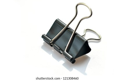 An image of black paper clips on white