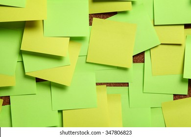Image of blank green and yellow sticky notes on cork bulletin board