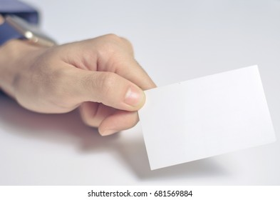 Image of a blank white piece of paper holding by a man hand. White background. Business card and name card. blurry.