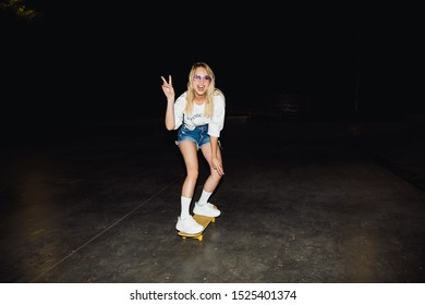 Image of blonde caucasian girl in streetwear smiling and riding skateboard at night outdoors