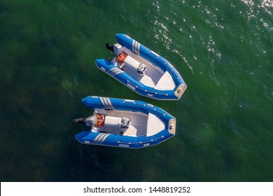 image of blue inflatable motorboats in the sea, top view