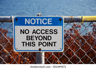 An image of a blue no access sign on a chain link fence.