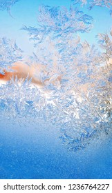 Image of blue texture patterns of frozen water crystals on the window pane in frosty winter in Christmas close-up