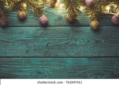 Image of blue wooden surface with burning New Year's garland, Christmas balls,