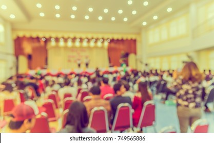 image of blur people looking to kid 's show on stage at school for background usage . (vintage tone)