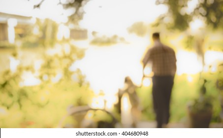 image of blur people stand beside river and green garden on day time for background usage . (vintage tone)