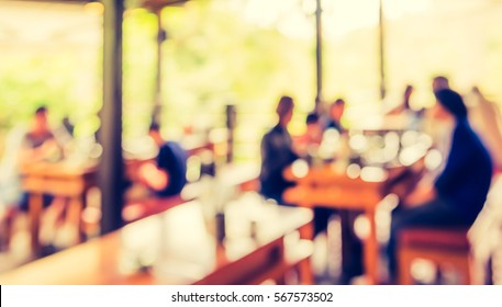 image of blur restaurant or coffee shop on day time with bokeh for background usage. (vintage tone)