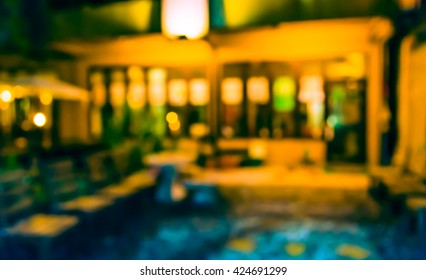 image of blur restaurant in night time for background usage . (vintage tone)