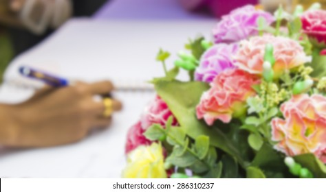 Image blur style, sign a wedding guestbook with a pen.