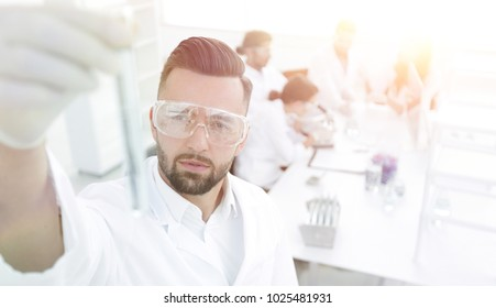 image is blurred. young scientist holding tube with the reagents