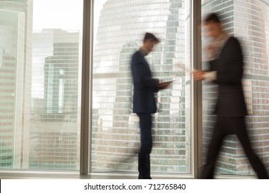Image of blurry silhouettes of office workers hurrying in business past large window with city view in modern office. Fast and tense rhythm of modern business life, busy businessmen, economical grow