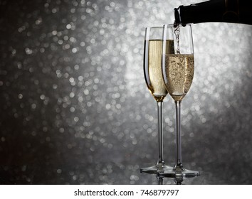 Image of bottle with champagne flowing in wine glasses on gray background