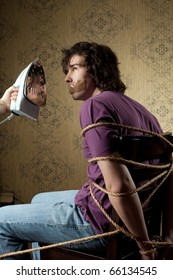 An image of a bound man on a chair and iron